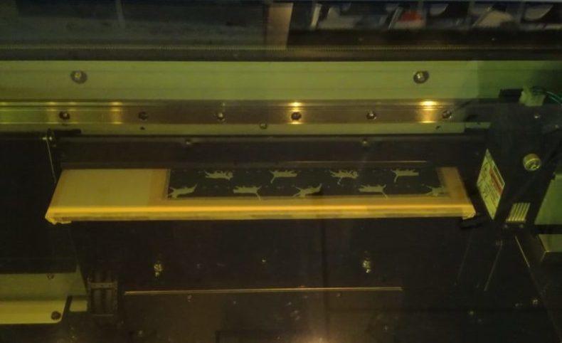UVプリンタでインク透過防止のホワイトインクを印刷していく。